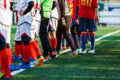 Νέο dribble αγοριών ποδοσφαιριστών, σφαίρα ποδοσφαίρου λακτίσματος στο παιχνίδι Αγόρια κόκκινο άσπρο sportswear που τρέχει στο γή στοκ φωτογραφία