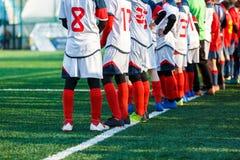 Νέο dribble αγοριών ποδοσφαιριστών, σφαίρα ποδοσφαίρου λακτίσματος στο παιχνίδι Αγόρια κόκκινο άσπρο sportswear που τρέχει στο γή στοκ φωτογραφίες