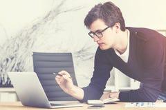 Νέο enterpreneur στα γυαλιά και την εργασία πουλόβερ, που τονίζεται Στοκ φωτογραφία με δικαίωμα ελεύθερης χρήσης