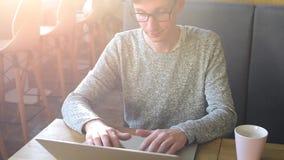 Νέο freelancer που λειτουργεί στον καφέ στο lap-top απόθεμα βίντεο