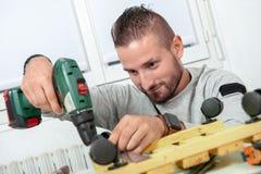 Νέο handyman χρησιμοποιώντας ηλεκτρικό τρυπάνι, DIY στο σπίτι στοκ εικόνα