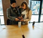 Νέο iPhone 8 και iPhone 8 συν στη Apple Store με το choosin κοριτσιών Στοκ Εικόνες