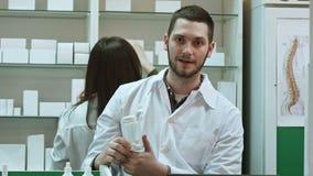 Νέο malepharmacist που κρατά ένα άσπρο κενό μπουκάλι των χαπιών, που προάγει την ιατρική, η εργασία συναδέλφων του φιλμ μικρού μήκους