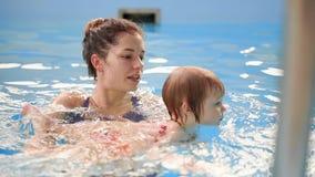 Νέο mom στη λίμνη που παίζει με την κόρη μωρών της σε σε αργή κίνηση Αθλητική οικογένεια που συμμετέχεται σε έναν ενεργό τρόπο ζω απόθεμα βίντεο