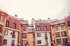 Νέο multi-storey κατοικημένο κτήριο Σύγχρονο σπίτι που βάφεται στα κόκκινα και πορτοκαλιά χρώματα Στοκ εικόνα με δικαίωμα ελεύθερης χρήσης