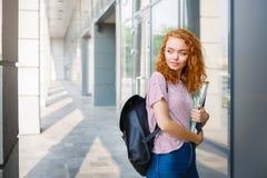 Νέο redhead κορίτσι σπουδαστών με ένα σακίδιο πλάτης και τα σημειωματάρια Στοκ Φωτογραφία