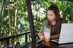 Νέο smartphone λαβής γυναικών στον καφέ καφέ, το άσπρους lap-top και τον πάγο στοκ εικόνες
