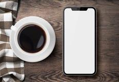 Νέο smartphone παρόμοιο με το iphone Χ τοπ άποψη σχετικά με τον παλαιό ξύλινο πίνακα με το ύφασμα και τον καφέ Στοκ φωτογραφίες με δικαίωμα ελεύθερης χρήσης