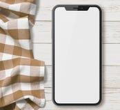 Νέο smartphone παρόμοιο με το iphone Χ τοπ άποψη σχετικά με τον παλαιό ξύλινο πίνακα με το ύφασμα Στοκ φωτογραφία με δικαίωμα ελεύθερης χρήσης