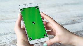 Νέο smartphone χρήσεων γυναικών με την πράσινη οθόνη απόθεμα βίντεο