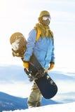 Νέο snowboarder με τον ήλιο πίσω από τον που παίρνει έτοιμο να αναρριχηθεί επάνω στο βουνό Στοκ Φωτογραφία