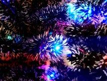 Νέο tinsel έτους με τα φω'τα νέου σε μια κινηματογράφηση σε πρώτο πλάνο χριστουγεννιάτικων δέντρων στοκ φωτογραφίες