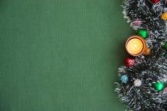 Νέο tinsel έτους ` s, ένα καίγοντας κερί σε ένα πράσινο υπόβαθρο Στοκ φωτογραφία με δικαίωμα ελεύθερης χρήσης