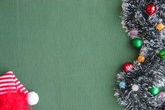 Νέο tinsel έτους ` s, γιρλάντα, σφαίρες και μια κόκκινη ΚΑΠ σε ένα πράσινο υπόβαθρο Θέση για την επιγραφή Στοκ Φωτογραφία