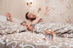 Νέο wakeup ζευγών στο κρεβάτι Στοκ Φωτογραφίες
