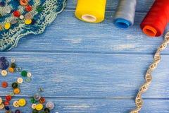 Νήματα και κουμπιά, ταινία εκατοστόμετρων σε ένα μπλε ξύλινο υπόβαθρο στοκ φωτογραφία