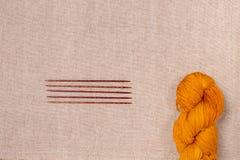 Νήμα του κόκκινος-κίτρινου χρώματος με τις ξύλινες πλέκοντας βελόνες Στοκ Εικόνα