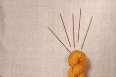 Νήμα του χρώματος βερίκοκων με τις ξύλινες πλέκοντας βελόνες Στοκ φωτογραφία με δικαίωμα ελεύθερης χρήσης