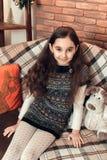 Νίκαια λίγο κορίτσι brunette με τη μακρυμάλλη συνεδρίαση σε έναν καναπέ στο CH Στοκ εικόνες με δικαίωμα ελεύθερης χρήσης