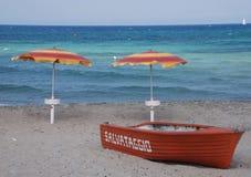 Ναυαγοσωστική λέμβος και δύο ομπρέλες παραλιών Στοκ Φωτογραφίες