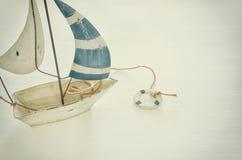 ναυτική έννοια με την άσπρη διακοσμητική βάρκα πανιών πέρα από τον άσπρο ξύλινο πίνακα φιλτραρισμένη τρύγος εικόνα Στοκ Εικόνες