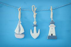 ναυτική έννοια με τις διακοσμήσεις τρόπου ζωής θάλασσας: ένωση βαρκών και αγκύρων πανιών σε μια σειρά πέρα από το μπλε ξύλινο υπό Στοκ φωτογραφία με δικαίωμα ελεύθερης χρήσης