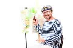 Ναυτικός ατόμων στην ΚΑΠ με τον καπνίζοντας σωλήνα, με τη σφαίρα και το χάρτη, στο μόριο Στοκ Φωτογραφίες