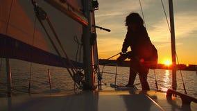 Ναυτικός γυναικών που εργάζεται sailboat στο ηλιοβασίλεμα, χόμπι, ενεργό υπόλοιπο απόθεμα βίντεο