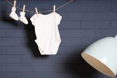 Ναυτικό, σκούρο μπλε τοίχος με την ένωση ενδυμάτων μωρών Στοκ Εικόνα