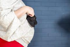 Ναυτικό, σκούρο μπλε τοίχος με τη έγκυο γυναίκα ενδυμάτων μωρών Στοκ Φωτογραφίες