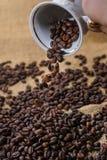 Να ανατρέψει έξω τα φασόλια καφέ από το φλυτζάνι Στοκ Εικόνα