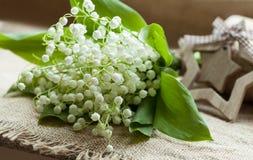 Να ανθίσει lilly της κοιλάδας στο αγροτικό κλωστοϋφαντουργικό προϊόν Στοκ Φωτογραφία