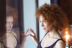 Να βάλει στον πειρασμό την αισθησιακή νέα γυναίκα που εξετάζει το παράθυρο Στοκ Φωτογραφίες