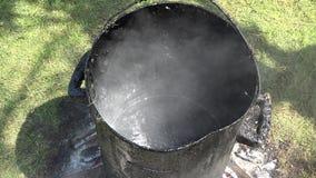 Να βράσει πίσσα στο βρώμικο βαρέλι χάλυβα που στέκεται στην πυρκαγιά 4K απόθεμα βίντεο