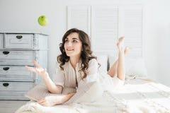 Να βρεθεί κοριτσιών στο κρεβάτι στο πρωί και ρίχνει τη Apple επάνω Στοκ Εικόνα