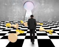 Να βρεθεί σκάκι χρημάτων με το περπάτημα επιχειρηματιών προς την κλειδαρότρυπα Στοκ Εικόνα
