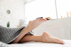 Να βρεθεί στα θηλυκά πόδια κρεβατιών κάτω από το κάλυμμα Στοκ Εικόνες