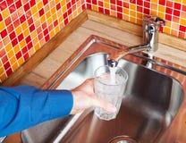 Να γεμίσει επάνω ένα γυαλί με το νερό από τη βρύση POV κουζινών Στοκ Εικόνες