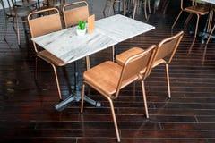 Να δειπνήσει μαρμάρινος πίνακας με τις καρέκλες μετάλλων ορείχαλκου Στοκ φωτογραφία με δικαίωμα ελεύθερης χρήσης