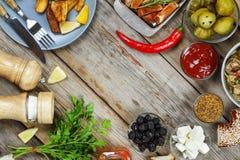 Να δειπνήσει πίνακας με το ψημένο στη σχάρα κρέας, τις αγροτικές πατάτες και τα παστωμένα αγγούρια Έννοια να φάει υπαίθρια Στοκ Φωτογραφίες