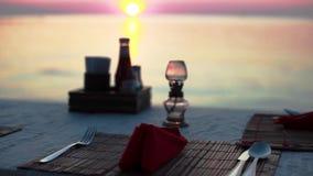 να δειπνήσει παραλιών Vew ενός πίνακα με τα μαχαιροπήρουνα σε ένα εστιατόριο παραλιών κατά τη διάρκεια του ηλιοβασιλέματος από τη φιλμ μικρού μήκους
