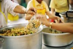 Να δώσει τα τρόφιμα στους επαίτες για να ανακουφίσει την πείνα: η έννοια της διανομής της βοήθειας στα συντροφικά ανθρώπινα οντα  στοκ φωτογραφίες