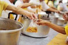 Να δώσει τα τρόφιμα στους επαίτες για να ανακουφίσει την πείνα: η έννοια της διανομής της βοήθειας στα συντροφικά ανθρώπινα οντα  στοκ φωτογραφία με δικαίωμα ελεύθερης χρήσης
