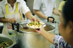 Να δώσει τα τρόφιμα στους επαίτες για να ανακουφίσει την πείνα: η έννοια της διανομής της βοήθειας στα συντροφικά ανθρώπινα οντα  στοκ φωτογραφία