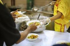 Να δώσει τα τρόφιμα στους επαίτες για να ανακουφίσει την πείνα: η έννοια της διανομής της βοήθειας στα συντροφικά ανθρώπινα οντα  στοκ εικόνα με δικαίωμα ελεύθερης χρήσης