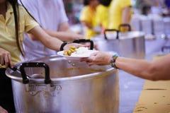 Να δώσει τα τρόφιμα στους επαίτες για να ανακουφίσει την πείνα: η έννοια της διανομής της βοήθειας στα συντροφικά ανθρώπινα οντα  στοκ εικόνα