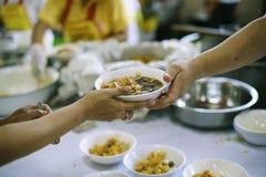 Να δώσει τα τρόφιμα στους επαίτες για να ανακουφίσει την πείνα: η έννοια της διανομής της βοήθειας στα συντροφικά ανθρώπινα οντα  στοκ εικόνες