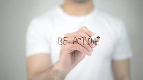 Να είστε ενεργός, άτομο που γράφει στη διαφανή οθόνη Στοκ φωτογραφίες με δικαίωμα ελεύθερης χρήσης