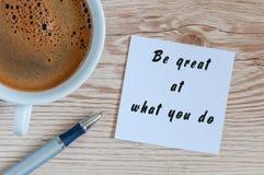 Να είστε μεγάλος σε αυτό που - κινητήρια έννοια στο σημειωματάριο με την κούπα πρωινού του καφέ Στοκ εικόνα με δικαίωμα ελεύθερης χρήσης