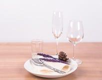Να δειπνήσει πίνακας που θέτει το άσπρο πιάτο με το λουλούδι, wineglass, τρύγος Στοκ Εικόνες